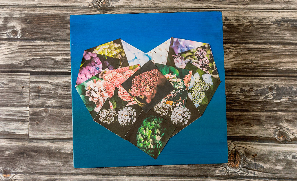 A heart shaped photo collage on a table.