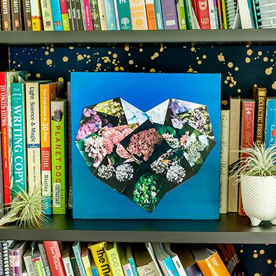A heart collage photo on a bookshelf.