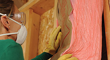 Person wearing protective gear installing insulation batts in a wall.