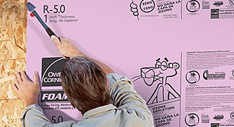 Person marking a sheet of foam board insulation.