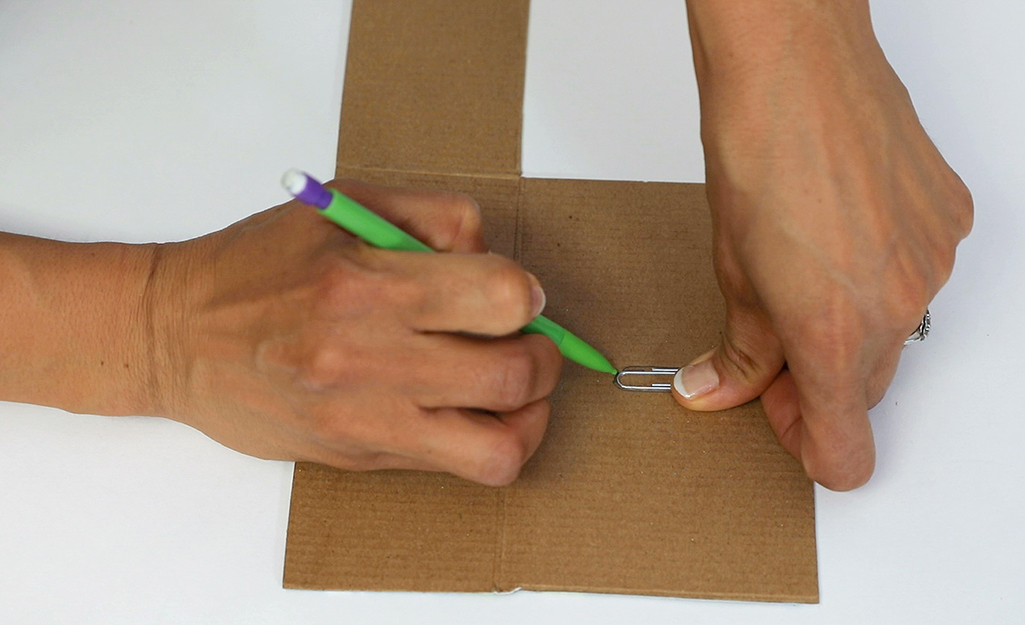 Someone drawing the shape of a paper clip onto a piece of cardboard.