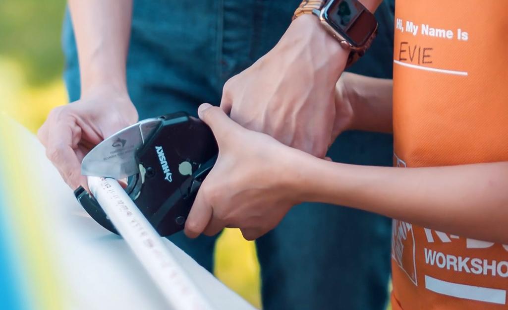 Một người lớn giúp một đứa trẻ cắt ống nhựa PVC.