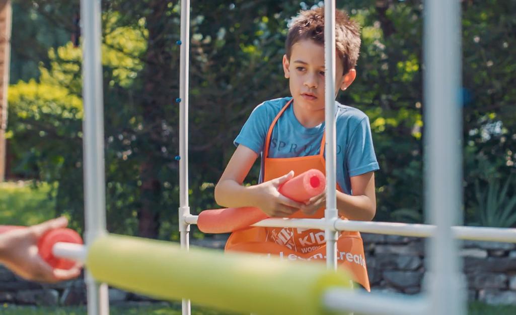 Một đứa trẻ đặt những miếng bánh mì hồ bơi trên một vòi phun nước dành cho trẻ em tự làm.