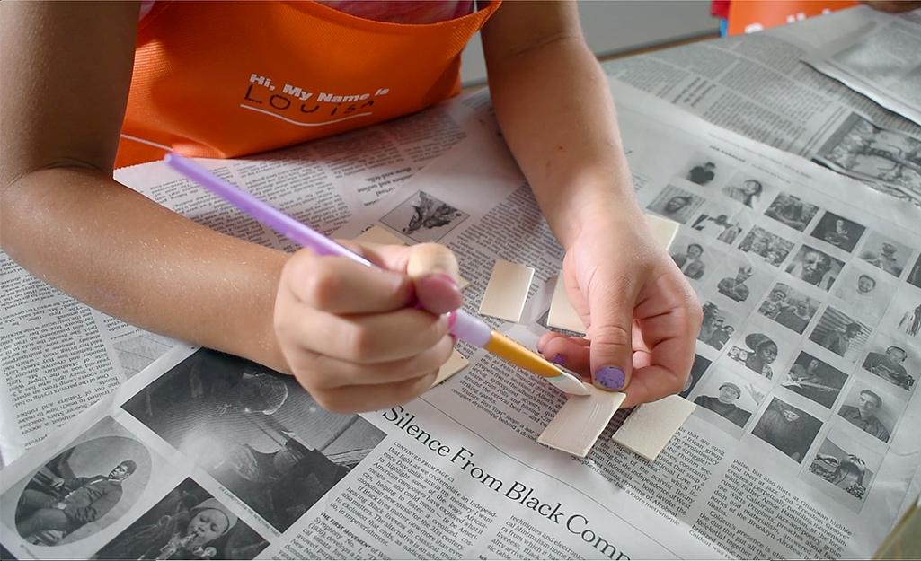 Bé vẽ những mảnh gỗ nhỏ.