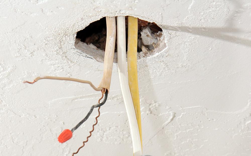 Hệ thống dây điện chiếu sáng nhô ra từ một lỗ trên trần nhà