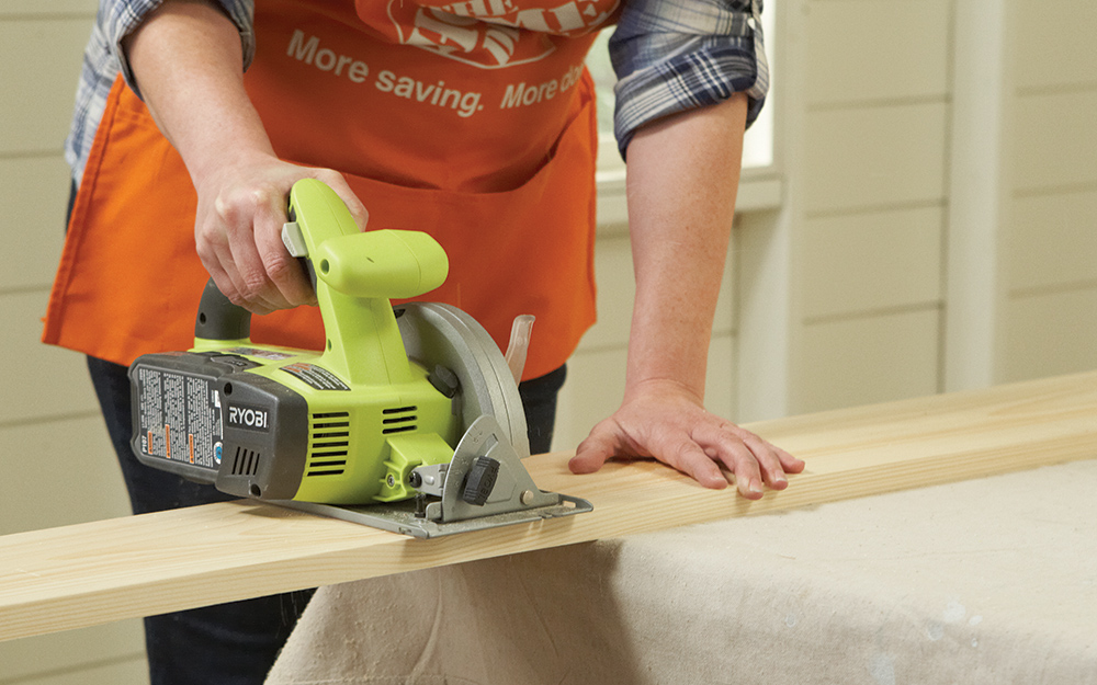 A person uses a saw to cut into a wood plank.