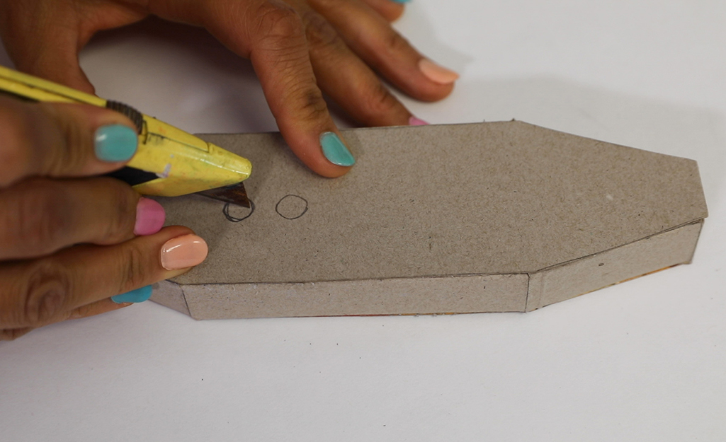 A person cutting holes in a piece of cardboard.