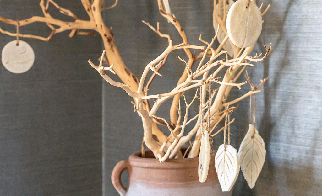 Salt dough leaf ornaments hanging on a decorative twig tree.