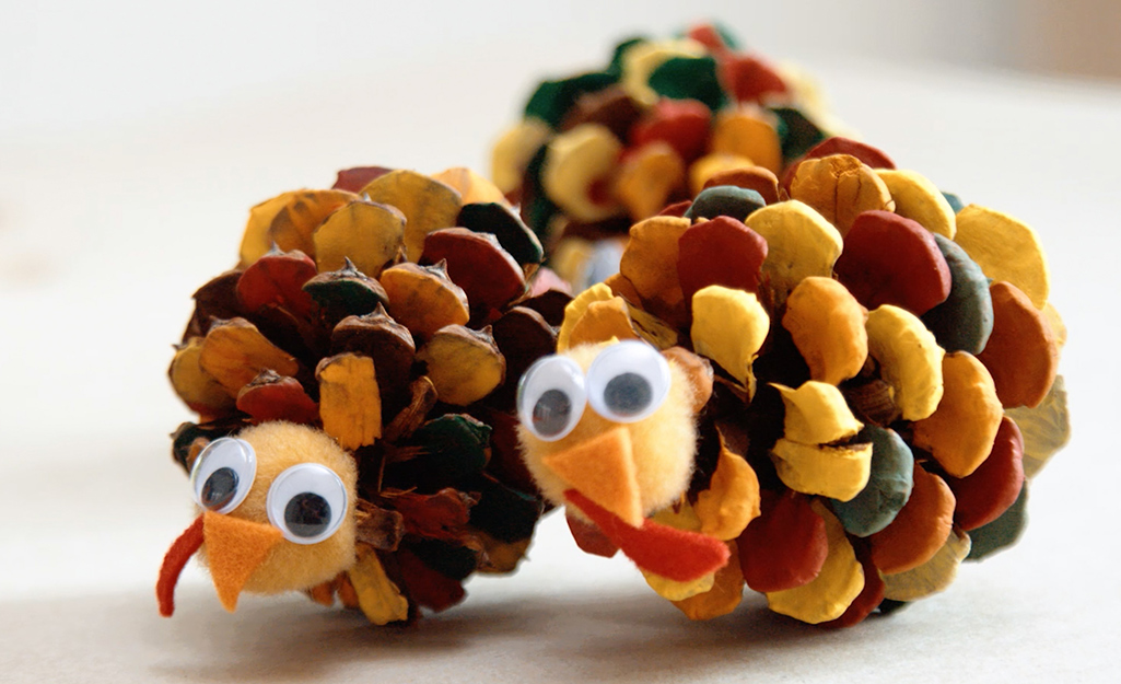 Two colorful turkey pinecones sitting on a table.