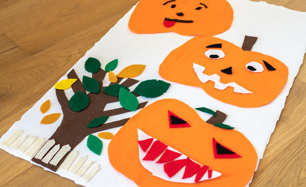 Felt pumpkin artwork lying on a table.