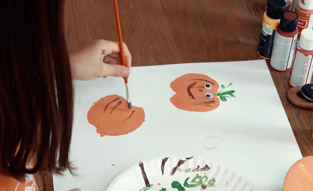 A person decorating a pumpkin imprint.