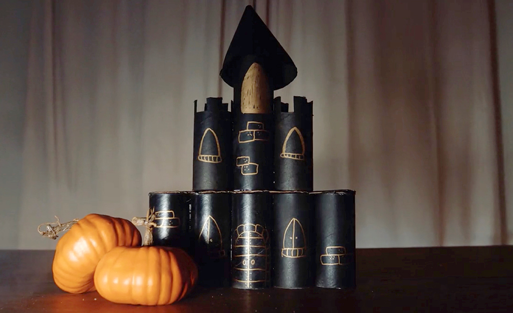 A completed haunted castle with pumpkins on a table.