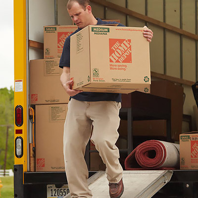 Man carrying a moving box from The Home Depot out of a Penske rental truck