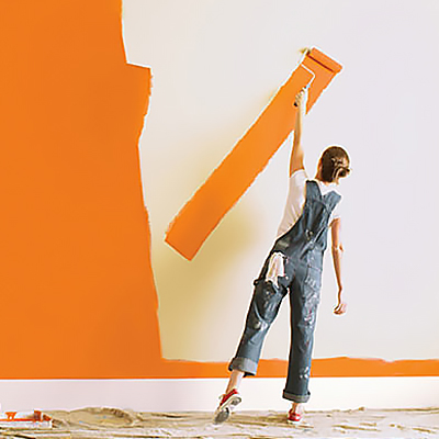 A person painting a wall with bright orange paint.