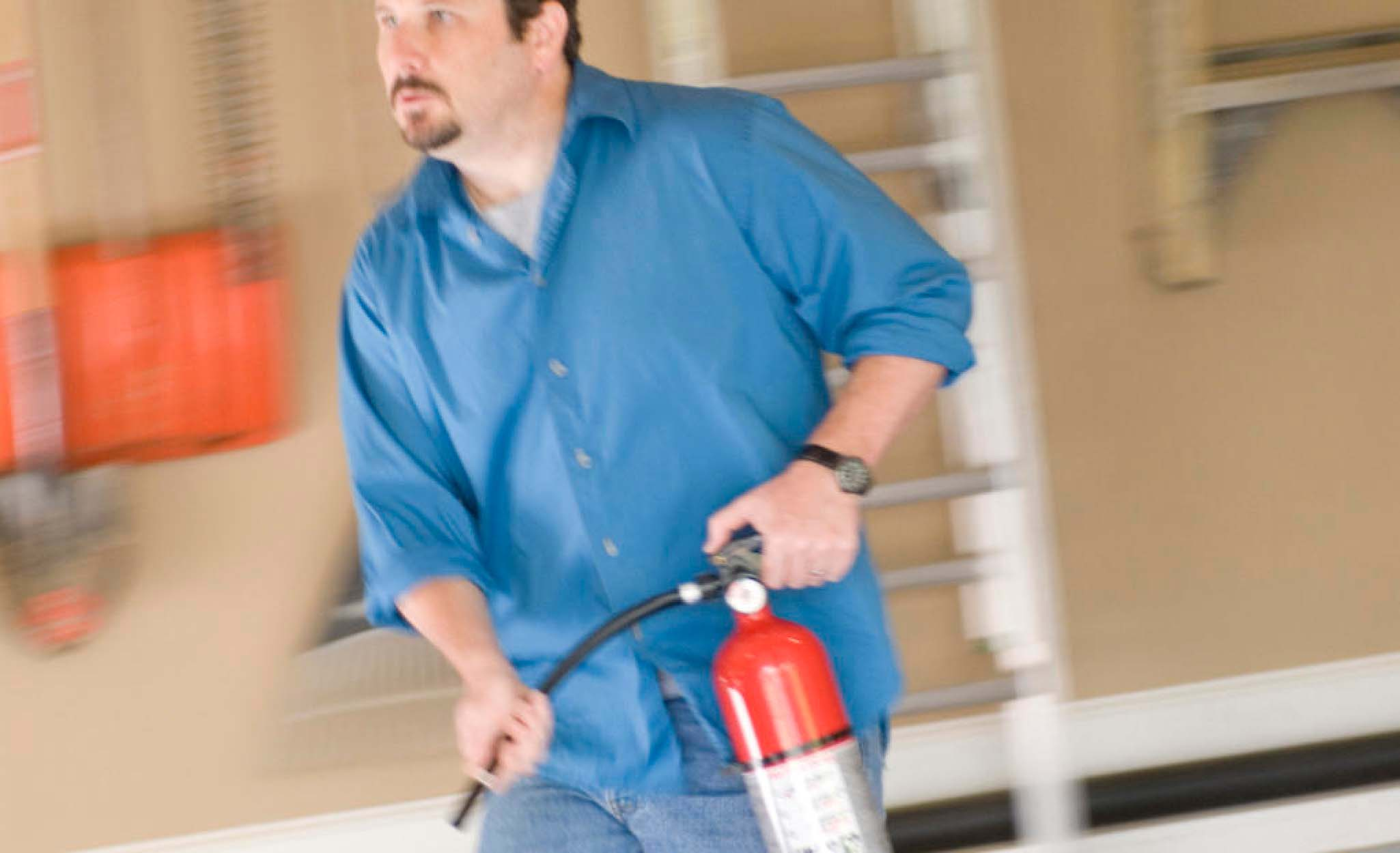 A man prepares to use a fire extinguisher.
