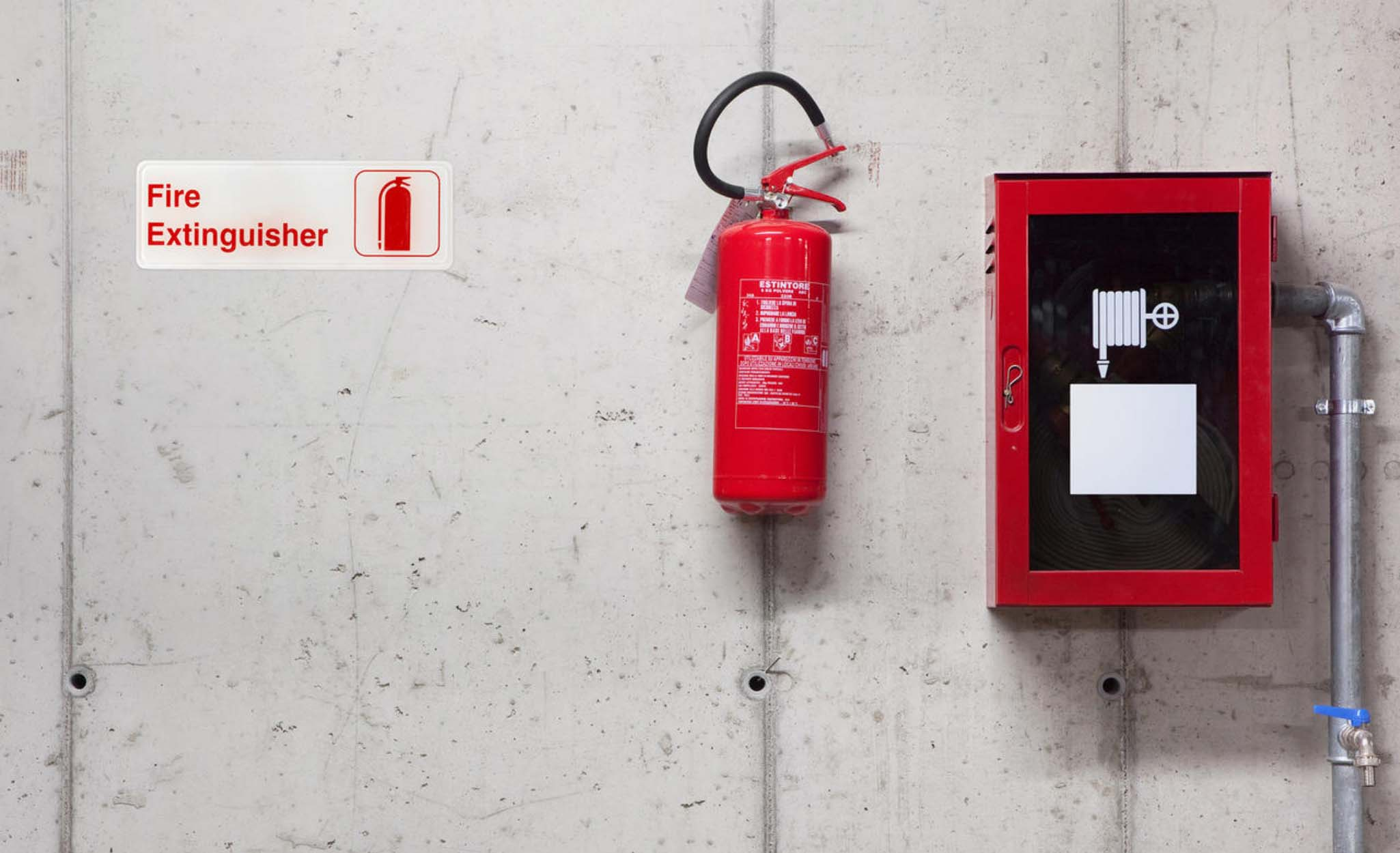 A fire extinguisher and signage hang on a wall.