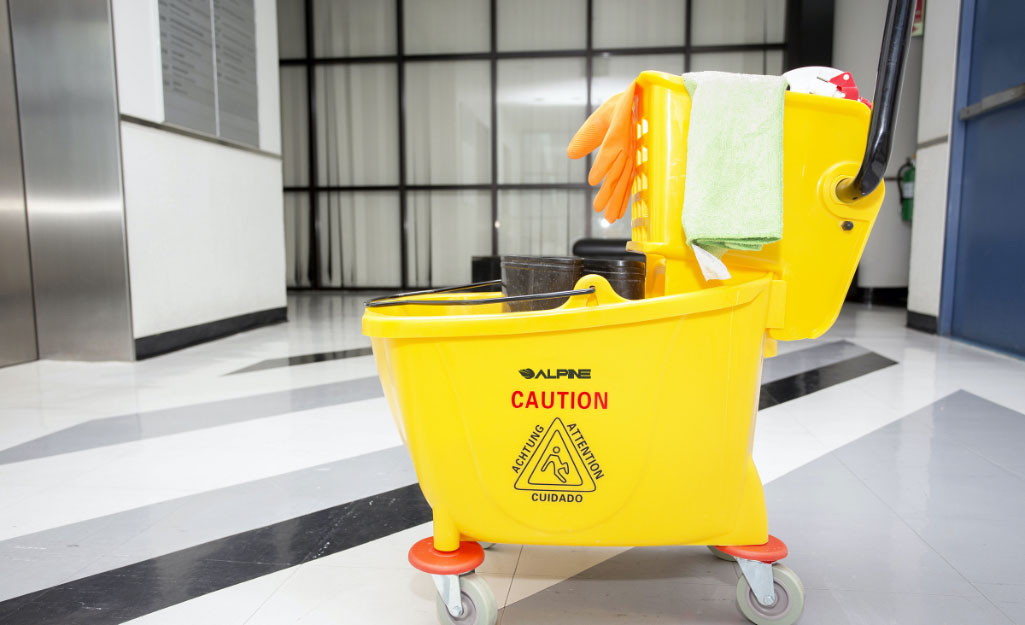 A mop bucket with a wringer in a commercial lobby