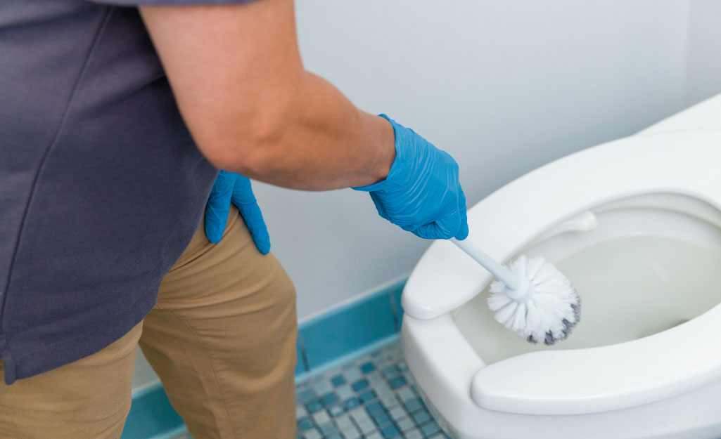 A worker cleans a toilet