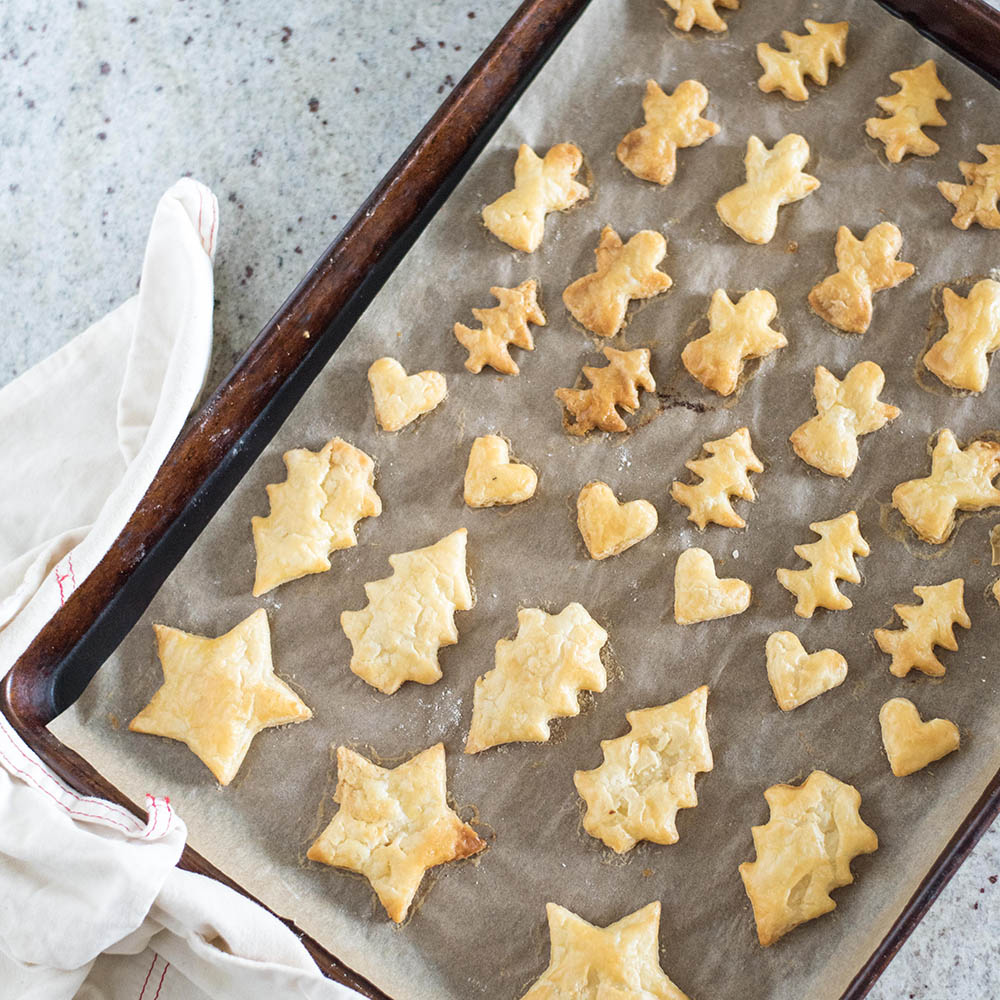 A cooked tray of pie dough cut into shapes.