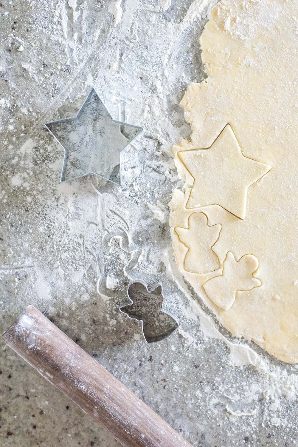 Freshly rolled out pie dough being cut into shapes with cookie cutters.