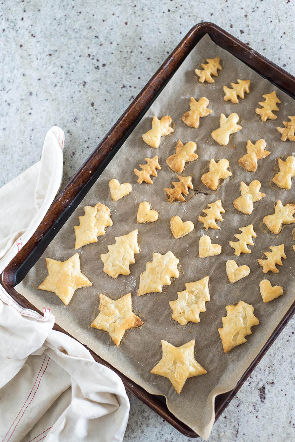 A pan of baked pie dough cut into shapes.