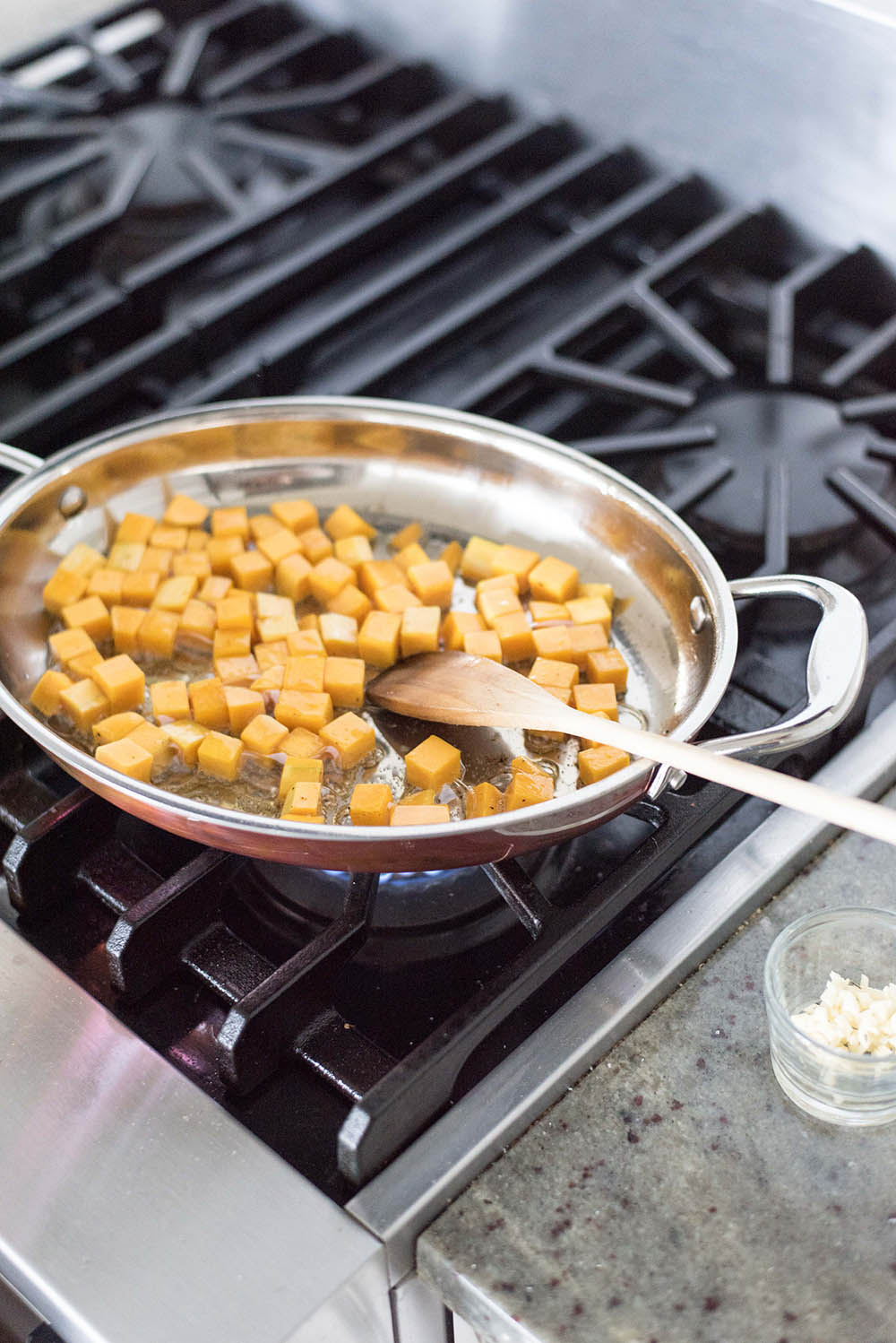 Diced butternut squash cooking on a stove.