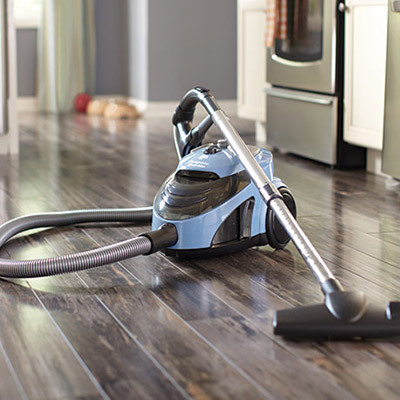 A canister vacuum on a hardwood kitchen floor