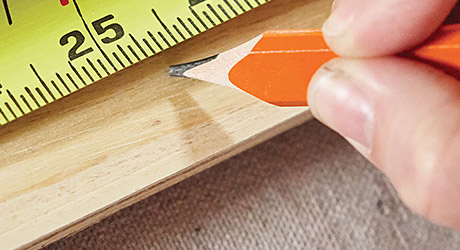 a person marks a piece of wood with a pencil