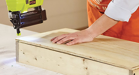 using a brad nailer to attach the plywood back to the frame