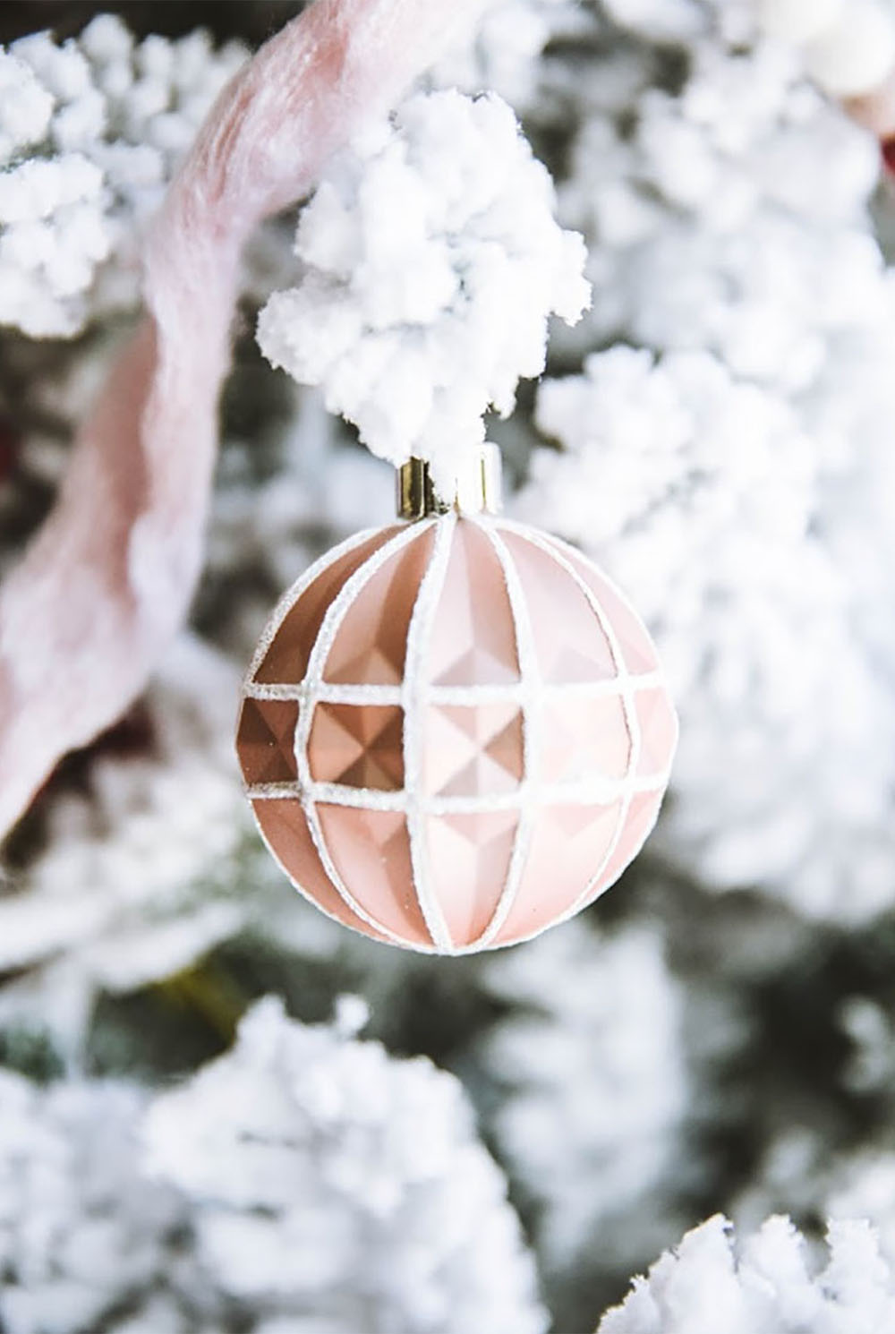A pink ornament with with detail hangs on a flocked Christmas tree branch.