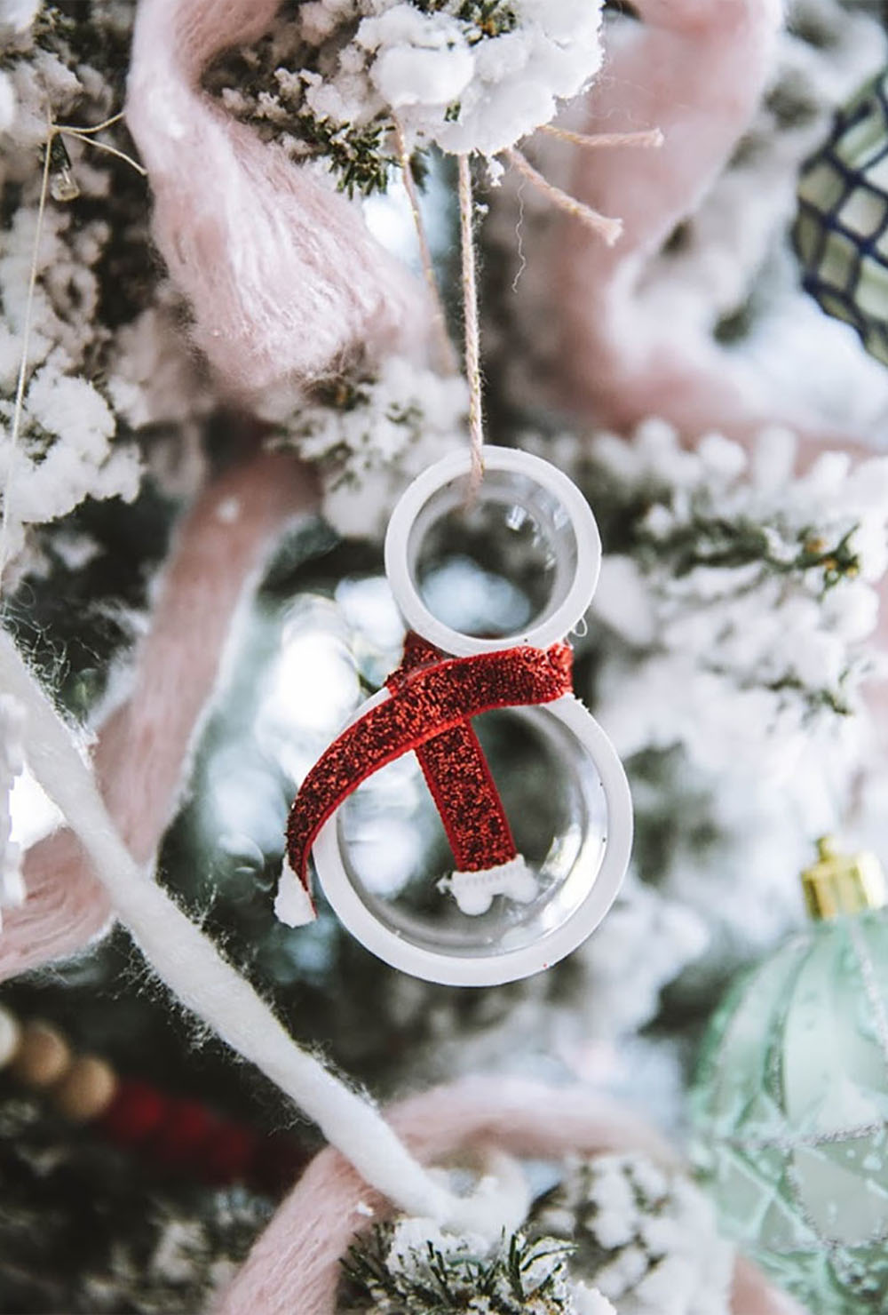 An ornament hanging on a Christmas tree with pink yarn.