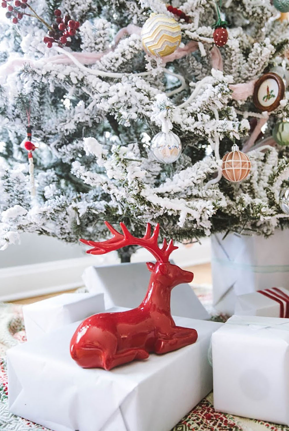 A red reindeer sitting on a wrapped gift under a Christmas Tree.