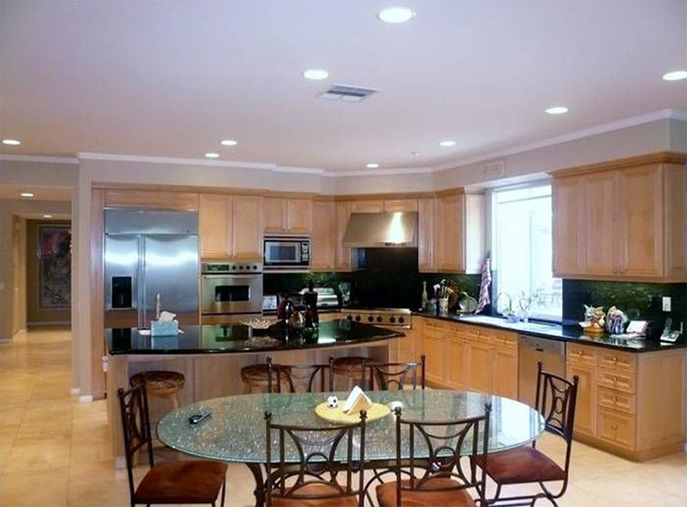 A kitchen with wooden cabinets, appliances and a glass dining table with 6 chairs.