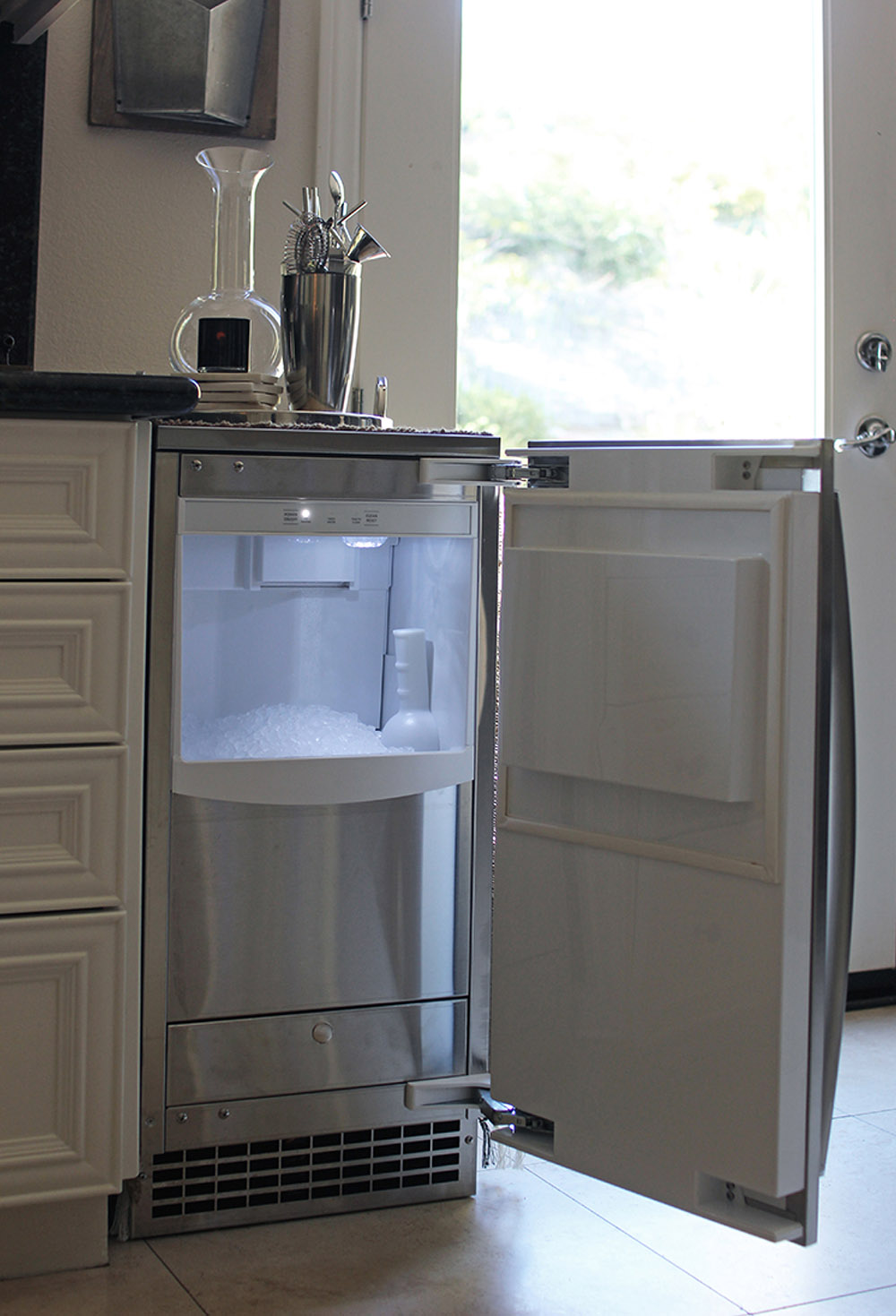 An open mini fridge attached to a home bar.