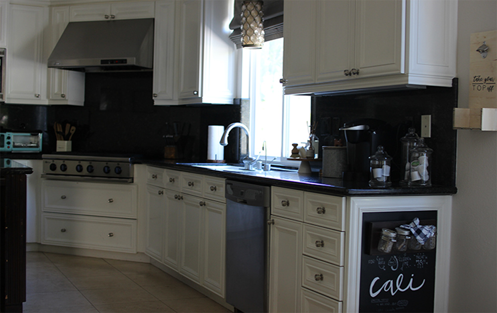 A kitchen with white cabinets, GE appliances and miscellaneous items on the countertops like a coffee maker.