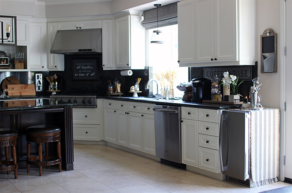 A kitchen with white cabinets, GE appliances, miscellaneous items on the countertops like a coffee maker and an island bar with barstools.