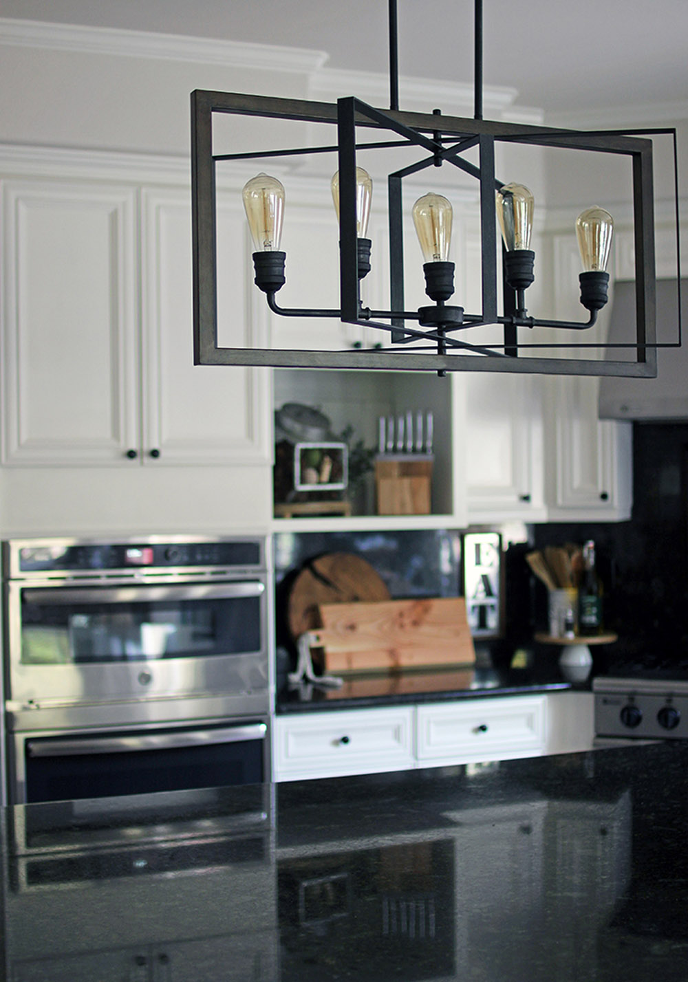 A black hanging light fixture in the middle of a kitchen with an over in the background.