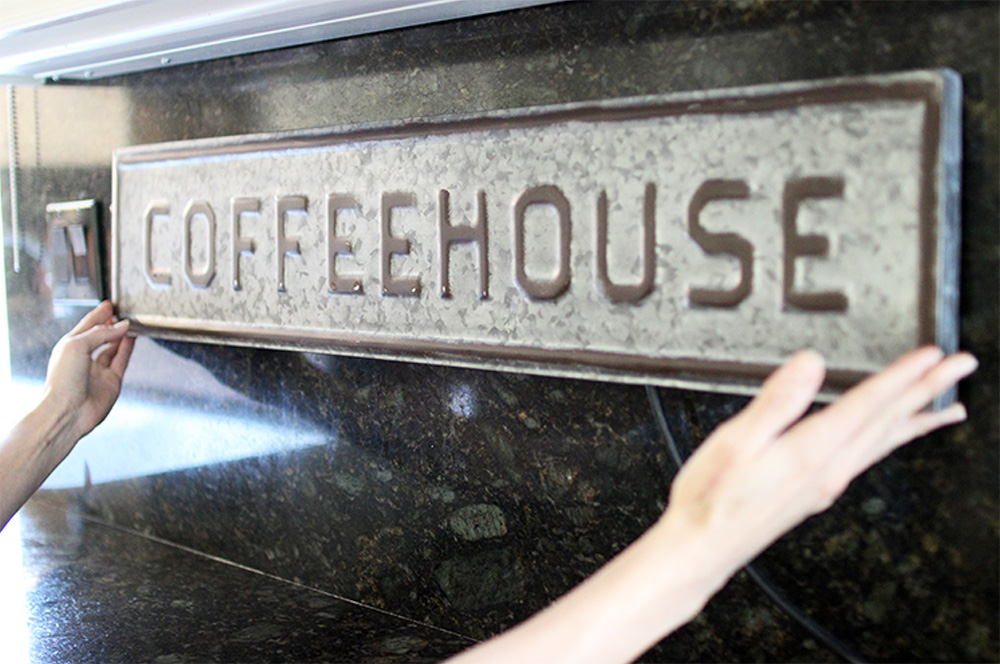 """A woman hanging a sign that says """"Coffeehouse"""" on marble backsplash."""