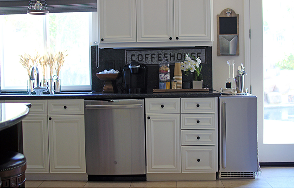 """A kitchen counter with a coffee area with a coffee machine, a """"coffeehouse"""" sign and other miscellaneous items."""