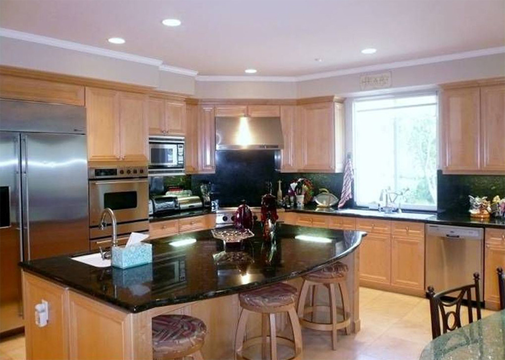 A kitchen with wooden cabinets, appliances and a wooden island bar with a black countertop and three barstools.