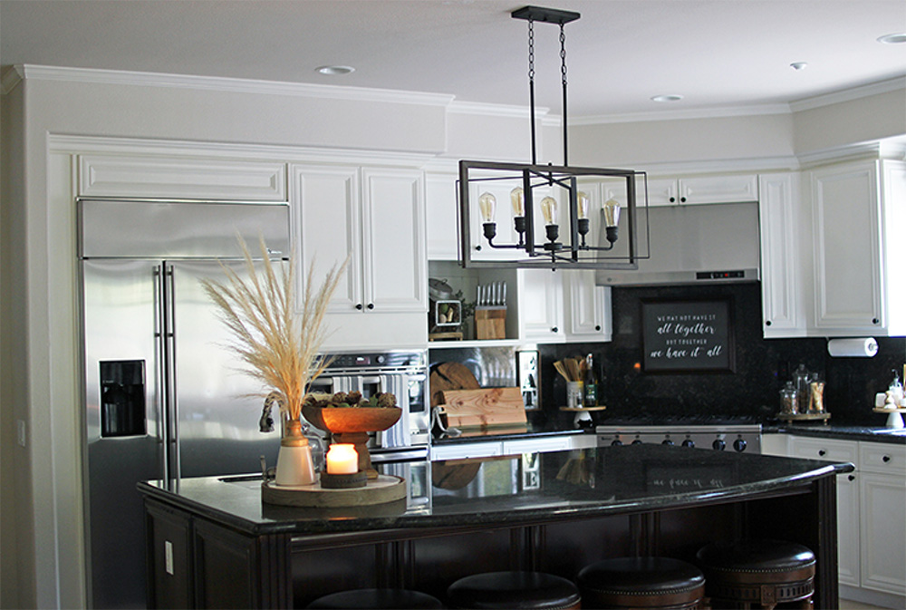 Kitchen with white cabinets, appliances, an island bar with four bar stools and a candle, and a hanging light fixture.