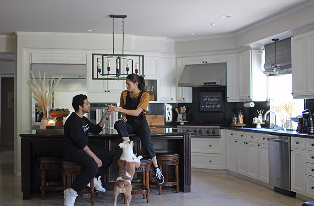 Two people and a dog in a kitchen with white cabinets, appliances, an island bar with four bar stools and a hanging light fixture.