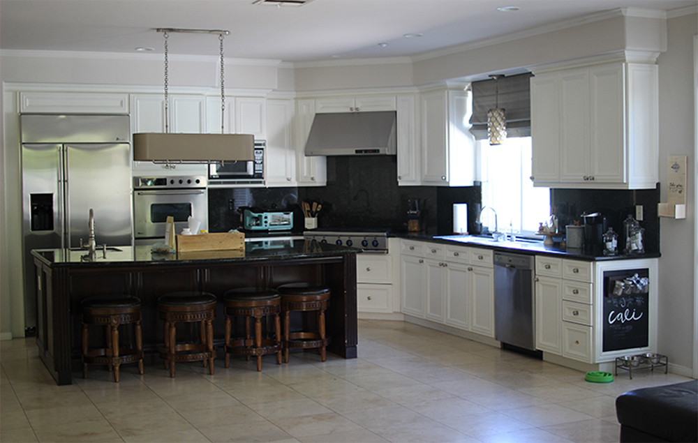 Kitchen with white cabinets, appliances and an island bar with four bar stools.