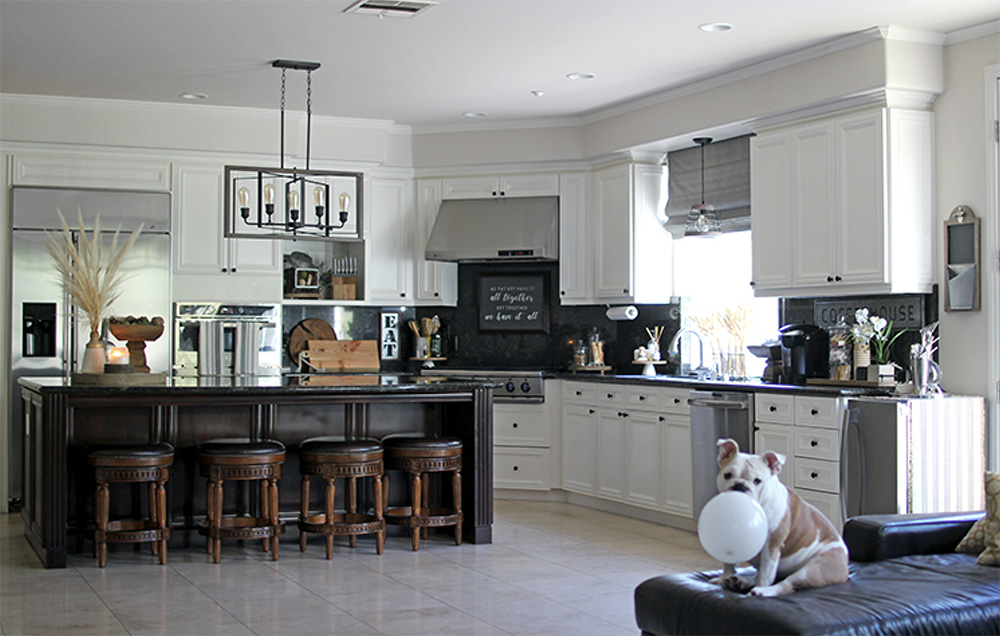 Kitchen with white cabinets, appliances, an island bar with four bar stools and a hanging light fixture.