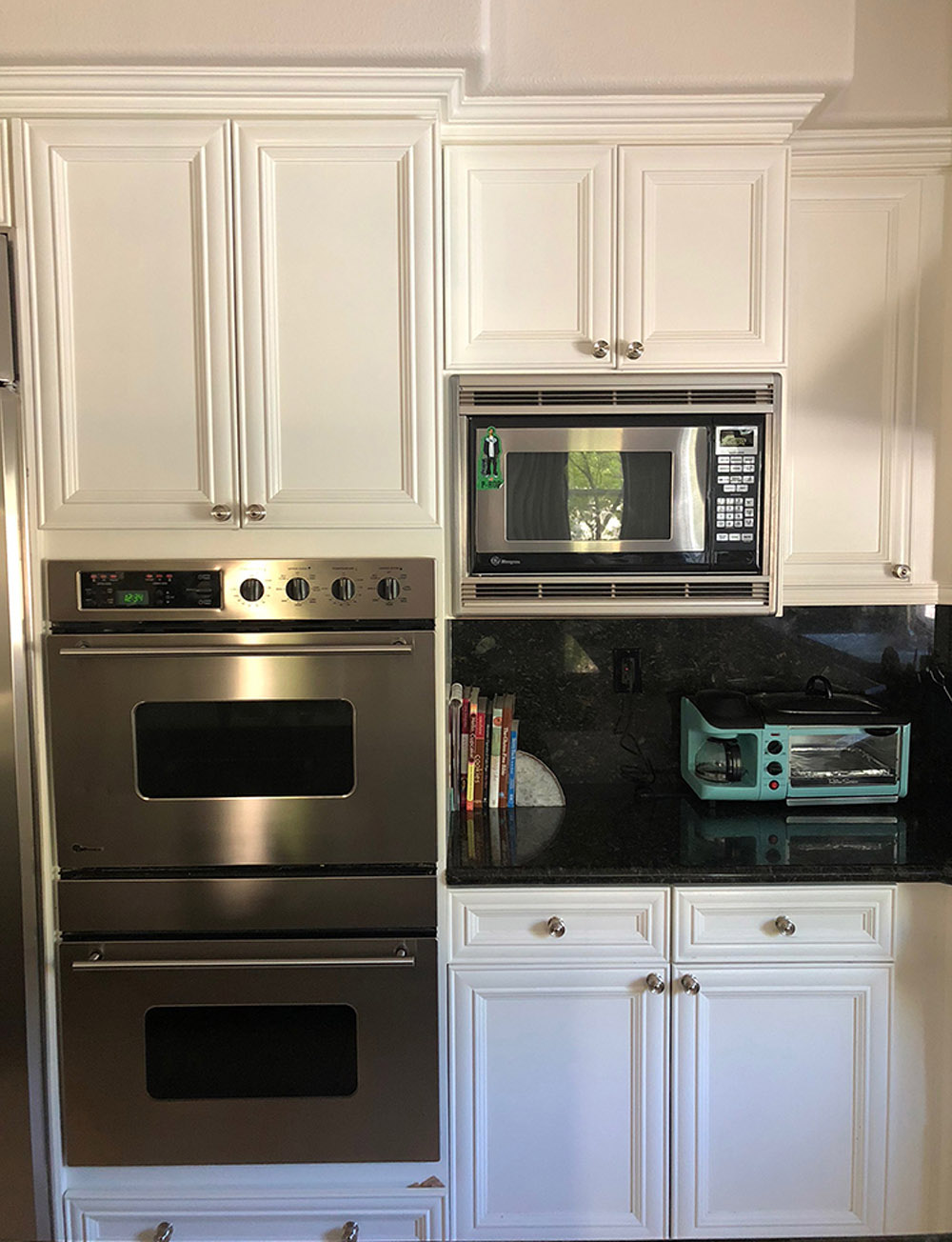 White kitchen cabinets, an over and a microwave.