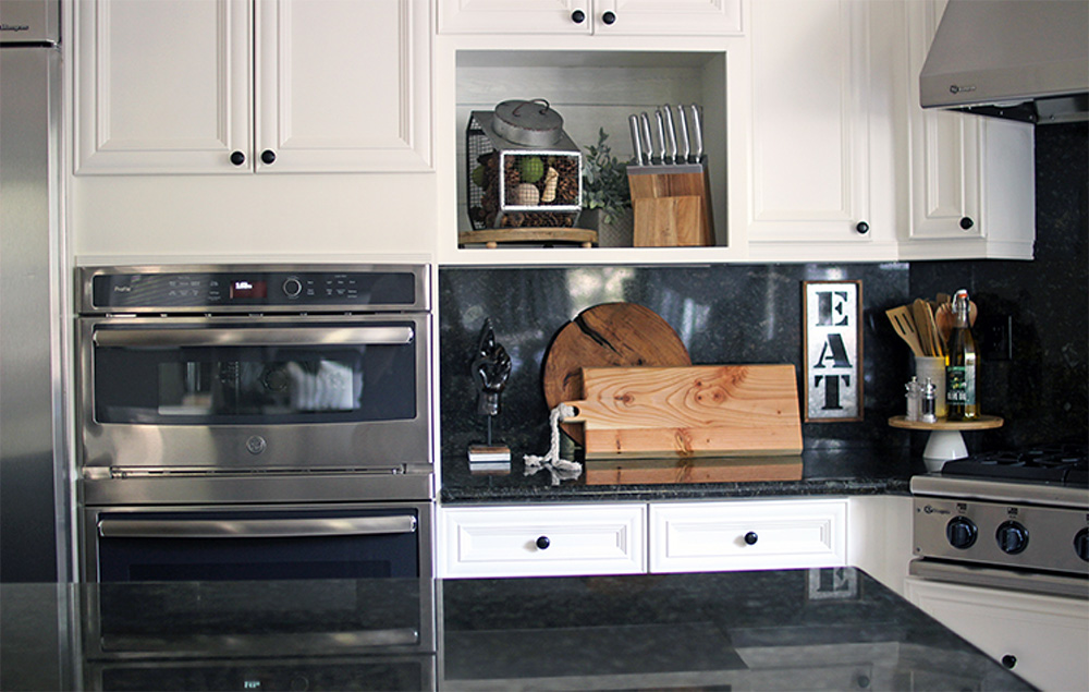 White kitchen cabinets, an oven, and decor placed on a kitchen counters like cutting boards and a Lazy Susan.