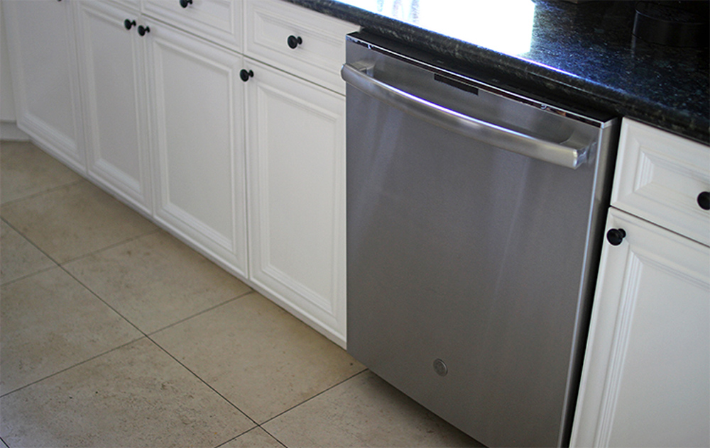 White kitchen cabinets and a dish washer.