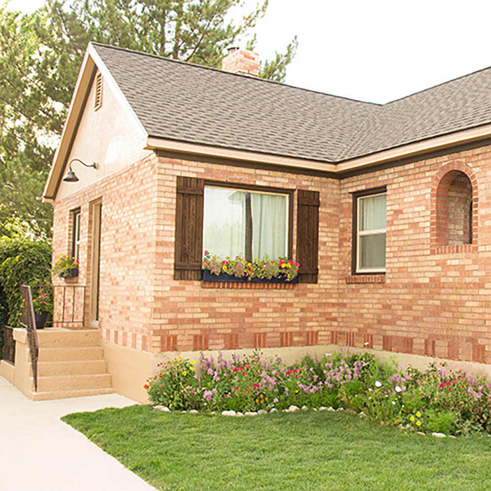 A brick home with a new roof and landscaped yard.