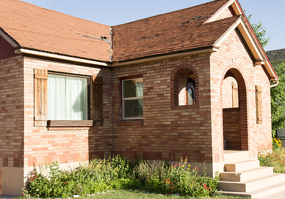 A brick home with an old roof and yard that has not been landscaped.