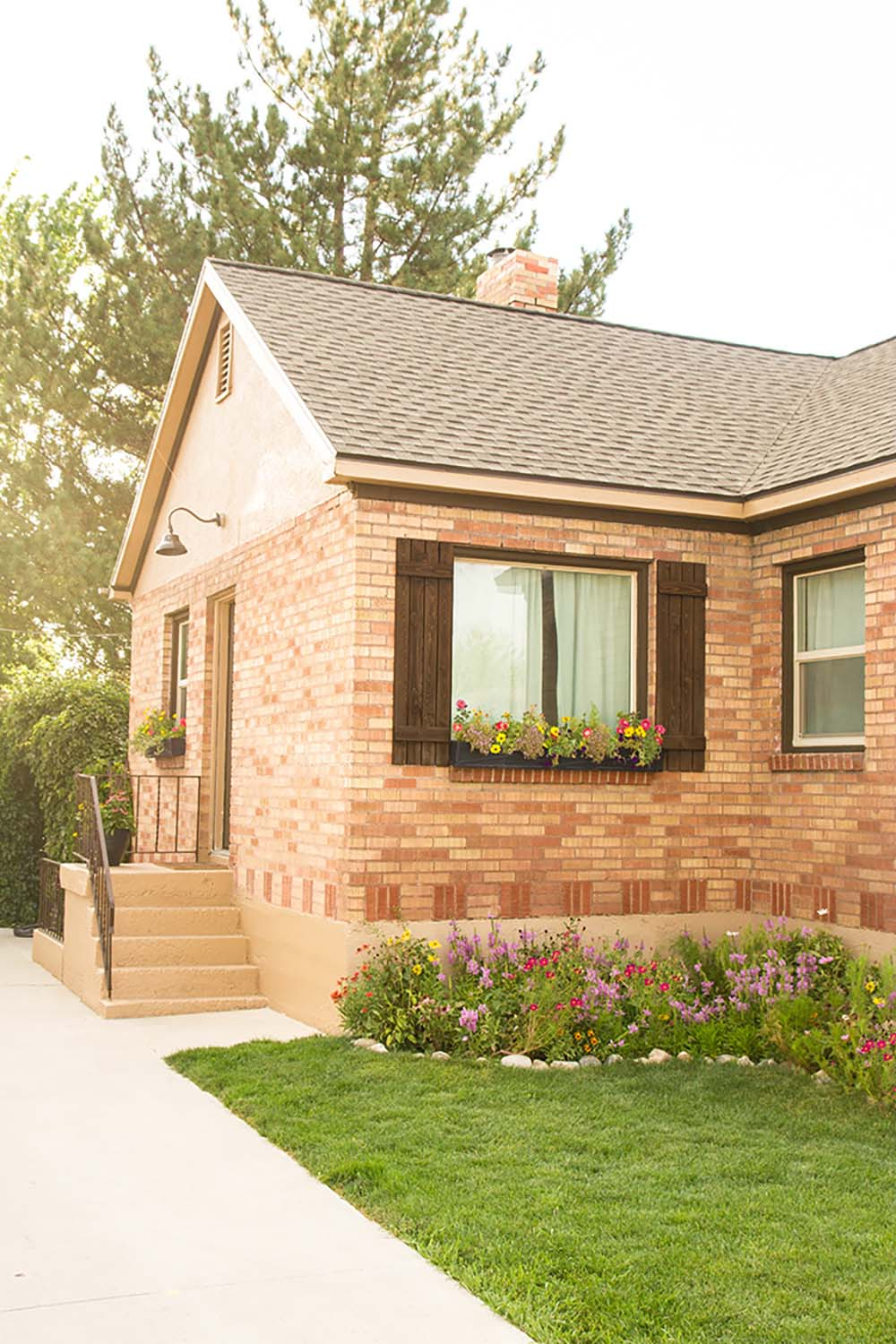The side entrance of a brick home with a landscaped yard.